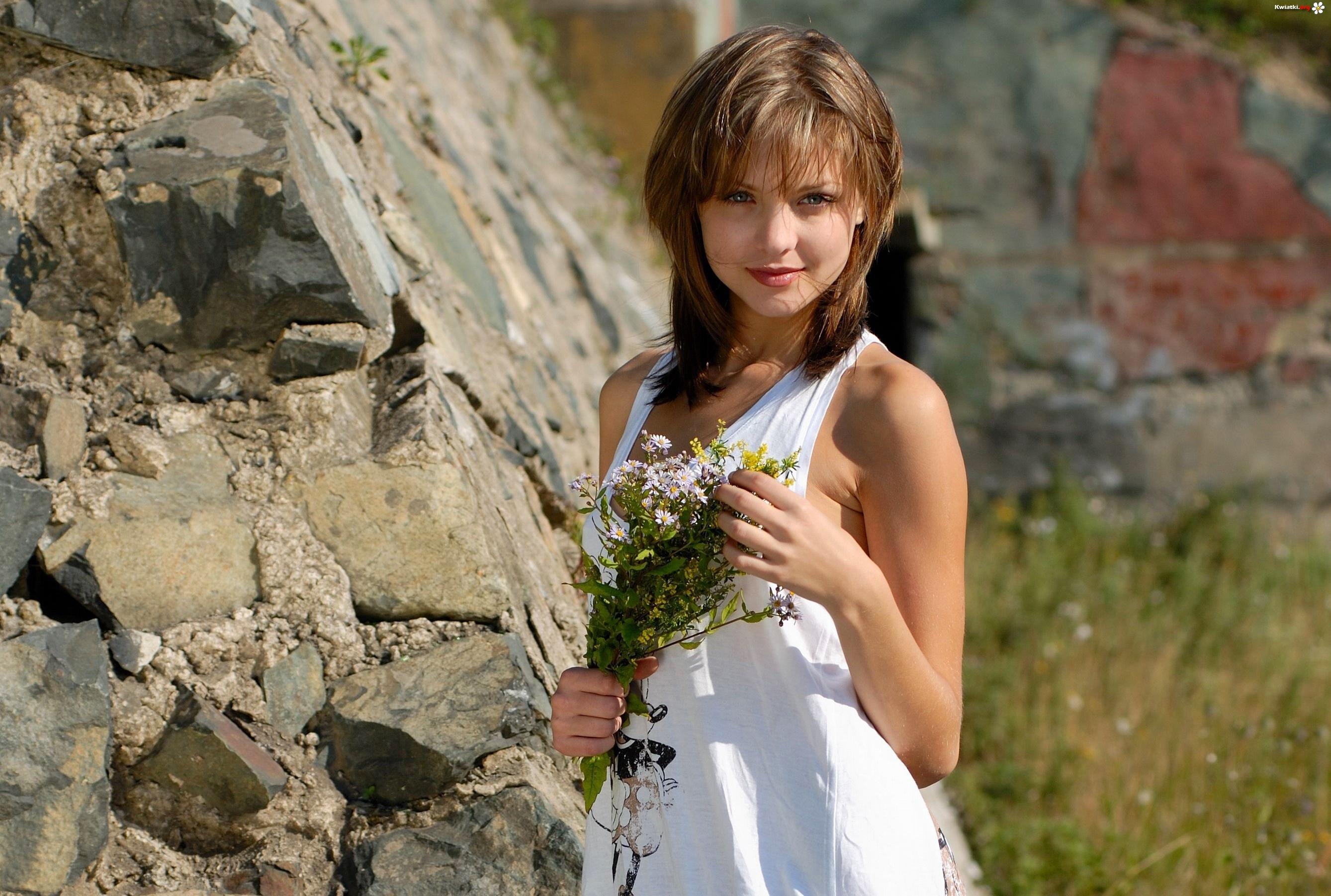 Kobieta z bukietem polnych kwiatów na łące